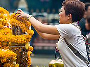 16 AUGUST 2016 - BANGKOK, THAILAND: A woman prays at Erawan Shrine one year after the shrine was bombed in the worst international terrorist attack in Thai history. On 17 August 2015, a bomb was set off at the Erawan Shrine, a popular tourist attraction and important religious shrine in the heart of the Bangkok shopping district. According to the Royal Thai Police  20 people were killed in the bombing and 125 injured. Thai Police arrested an alleged Uighur extremist for the bombing. The case against him is still pending in Thai courts. The shrine was repaired, rededicated and reopened to the public on 4 September 2015.      PHOTO BY JACK KURTZ