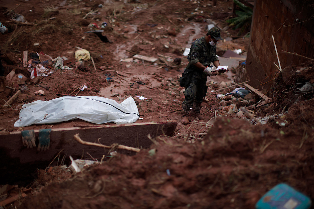 A man checks a notebook found near the body of Samara Coelho da Silva, 13, after removing her from an area afected by a landslide at Prainha neighborhood in Nova Friburgo, Brazil, Monday, Jan. 17, 2011. <br /> <br /> A series of flash floods and mudslides struck several cities in Rio de Janeiro State, destroying houses, roads and more. More than 900 people are reported to have been killed and over 300 remain missing in this, Brazil&rsquo;s worst-ever natural disaster.