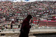 For a story by Ed Wong : CHINASICHUAN - Two journals in Sichuan<br /> Larung Gar, Sertar, Sichuan, China<br /> October 8th, 2016<br /> A Buddhist nun walking, prayer wheel in hand, walking past residential quarters in Larung Gar, a monastic camp where thousands of nuns and monks live and study. The Chinese government has requested that the number of nuns and monks this influential Buddhist academy be reduced by 5000.<br /> Gilles Sabri&eacute; for The New York Times