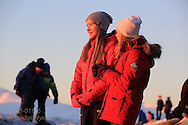 Girls watch return of the sun at Telegrafbukta at the south end of Tromsoya island on January 21st after two months with no sunrise; Tromso, Norway.