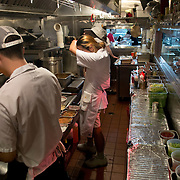Chef Danny Bowien, right, wipes his brow as he works in the kitchen of his restaurant, Mission Chinese, at its New York City location on the Lower East Side of Manhattan on Tuesday, July 31, 2012 in New York, NY...