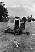 Family sitting by van in a field at Glastonbury.
