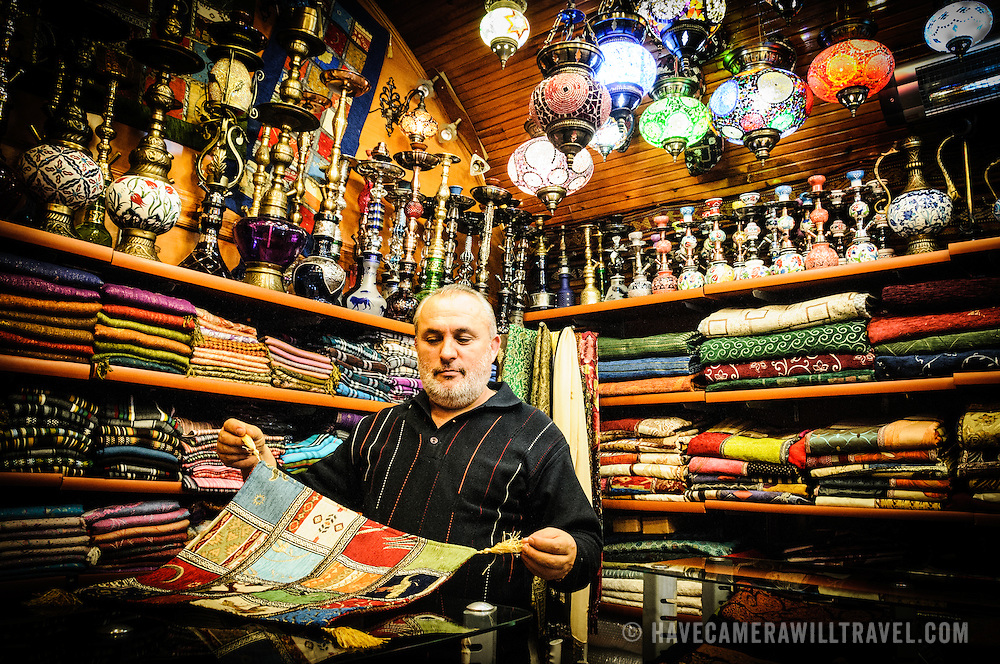 The salesman shows some of his silk scarves in his store at the Arastar Bazaar, a small bazaar next to the Sultanahment Camii (Blue Mosque) in Istanbul, Turkey.