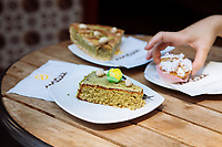 """NAPLES, ITALY - 13 JULY 2017: (From front to back) a A pistacchio caprese cake, a """"Ponti Nuovi"""" pastry and a pistacchio pastiera are seen here at Mazz, a patisserie in via dei Tribunali in Naples, Italy, on July 13th 2017."""