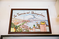 "NAPLES, ITALY - 12 SEPTEMBER 2018: Painted tiles with a panoramic view of Naples is seen here at the Taverna del Buongustaio, a tavern in Naples, Italy, on September 12th 2018.<br /> <br /> Taverna del Buongustaio was founded in the 1930s by wine producer of the province of Caserta. Gaetano Aiese and his daughter Giusy have been managing the tavern since 1996. Customers of the Taverna are professors of the nearby University, students, merchants and employees of via Toledo, the commercial street right around the corner. Giusy and her father Gaetano decided to invest in the traditional Neapolitan cuisine. ""I learned cooking from my dad. And my dad learned cooking from his mother"", Giusy said."