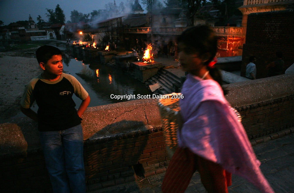 A boy stands on a bridge overlooking bodies burning on the ghats at the Pashupatinath Temple in Kathmandu on June 13, 2006. Pashupatinath is considered the most import temple in Nepal and it is where the Hindus burn their dead in traditional burial ceremonies. (Photo/Scott Dalton)