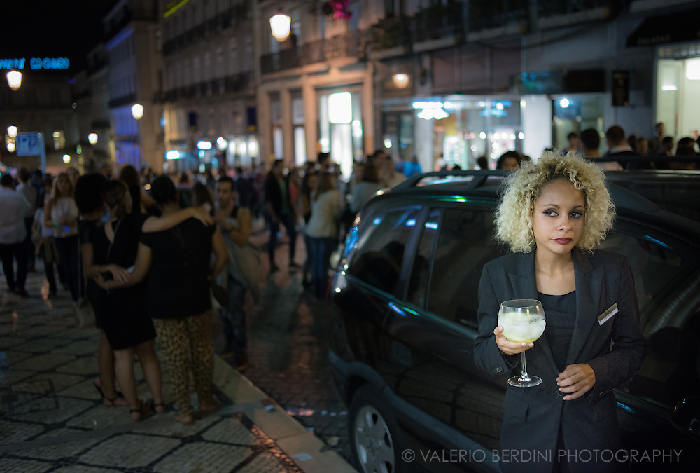 A Hugo Boss shop assistant takes a break with a drink. On the 11th of September 2014 most fashion shops in Lisbon stayed open at night offering drinks and discounts to customer.