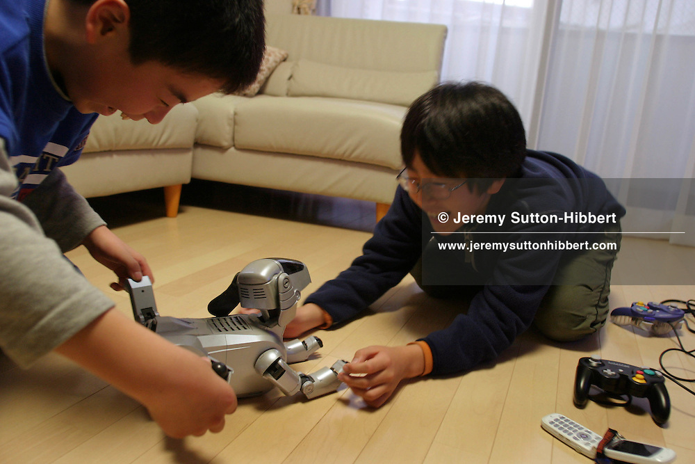 Japanese children playing with their Sony 'Aibo' robot dog, surrounded by other digital technology.