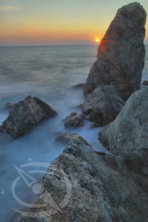The sun drops between the rocks in the Italian Riveria between the towns of Levanto and Monterossa.