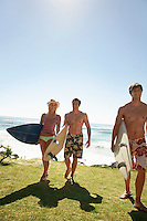 Three young people with surf board walking away from sea full length