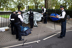 © Licensed to London News Pictures. 07/10/2019. London, UK. Police officers disassembles a gazebo after an Extinction Rebellion Roadblock was removed on Millbank . Photo credit: George Cracknell Wright/LNP