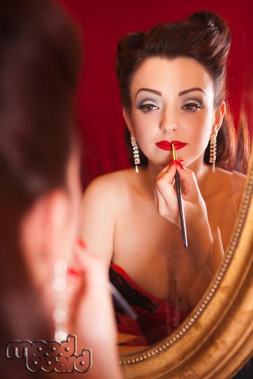 Showgirl applying lipstick