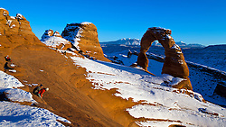 Groups of people viewing Delicate Arch with snow in winter at sunset, Arches National Park, Utah, United States of America