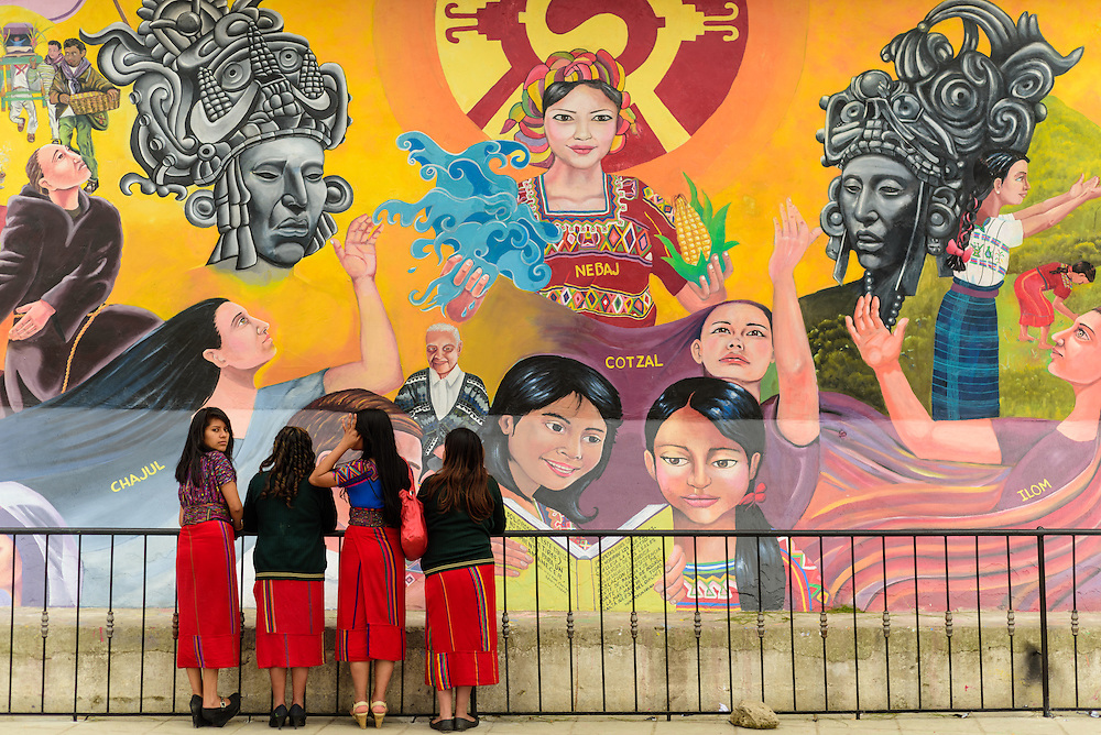 Three Ixil-girls standing in front of a wall mural in the town of Nebaj, Guatemala.