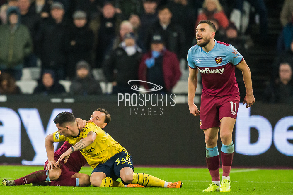 Gabriel Martinelli (Arsenal) & Mark Noble (Capt) (West Ham) righting themselves with Robert Snodgrass (West Ham) looking across to the ball during the Premier League match between West Ham United and Arsenal at the London Stadium, London, England on 9 December 2019.
