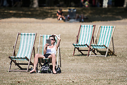 © Licensed to London News Pictures. 06/08/2018. London, UK. A woman reading while sat in the sun in a deck chair in St James's Park, as hot weather continues in the capital. Photo credit: Ben Cawthra/LNP