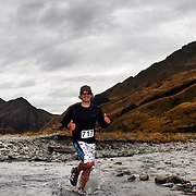 Runner Porentru Porentru crosses Moke Creek on the Ben Lomond High Country Station during the Pure South Shotover Moonlight Mountain Marathon and trail runs. Moke Lake, Queenstown, New Zealand. 4th February 2012. Photo Tim Clayton