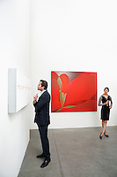 Full length of man standing in front of wall painting and woman
