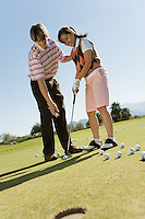 Golf Instructor Teaching Student to Putt