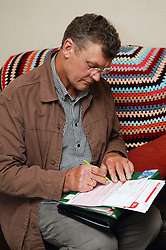 Welfare rights worker filling in financial details for a service user during home visit,