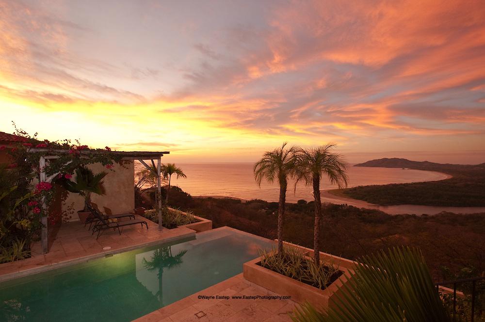 Villa pool and gazebo overlooking Playa Grande beach, Pacific Ocean and Las Baulas National Marine Park at sunset, Tamarindo, Costa Rica
