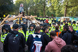 London, UK. 9 October, 2019. A climate activist from Extinction Rebellion sitting on top of a wooden structure used to block Birdcage Walk waits for a female police officer to arrive on a cherry picker to arrest her on the third day of International Rebellion protests.