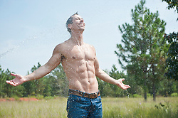 man without a shirt being sprayed with a garden hose outdoors in nature