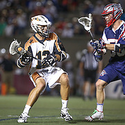 Justin Turri #12 of the Rochester Rattlers tries to get past Eric Martin #55 of the Boston Cannons during the game at Harvard Stadium on August 9, 2014 in Boston, Massachusetts. (Photo by Elan Kawesch)