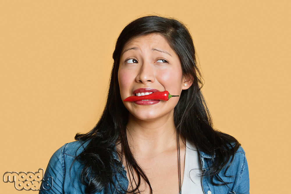 Young woman with red chili pepper in mouth over colored background