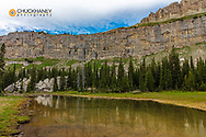 Pond reflects the Chinese Wall in the Bob Marshall Wilderness, Montana, USA