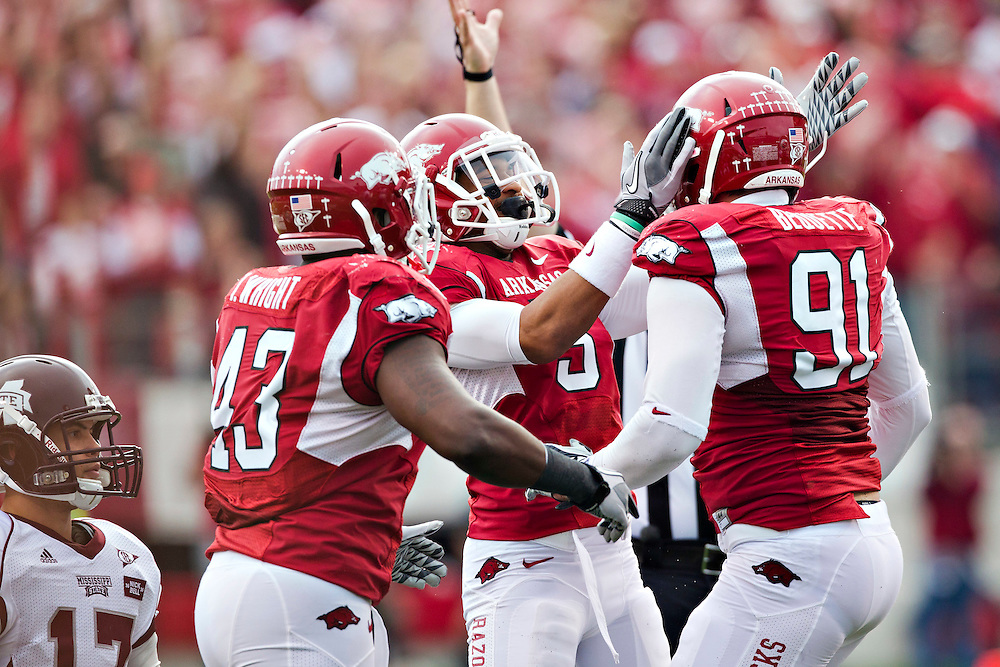 LITTLE ROCK, AR - NOVEMBER 19:   Jake Bequette #91, Tenarius Wright #43 and Tramain Thomas #5 of the Arkansas Razorbacks celebrate after a quarterback sack against the Mississippi State Bulldogs at War Memorial Stadium on November 19, 2011 in Little Rock, Arkansas.  The Razorbacks defeated the Bulldogs  44 to 17.  (Photo by Wesley Hitt/Getty Images) *** Local Caption *** Jake Bequette; Tenarius Wright; Tramain Thomas