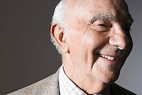 Senior man smiling in studio close up