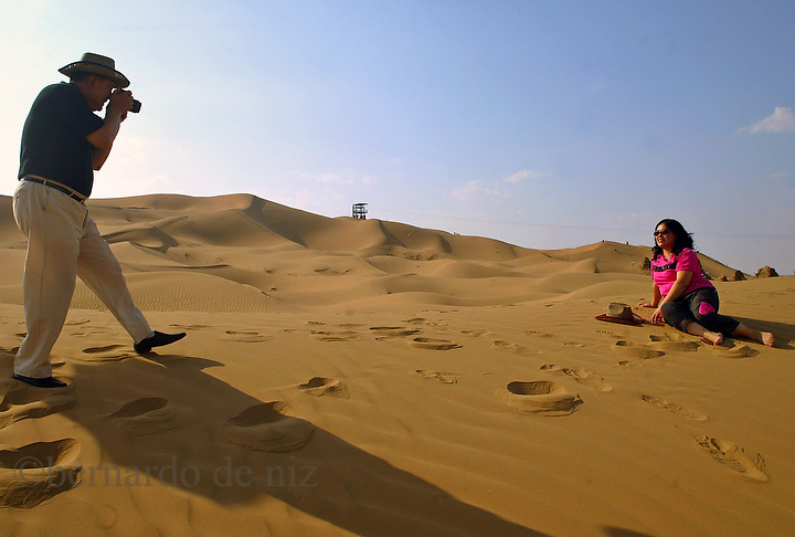 Chinese tourist are taking pictures of themselves in to the Jin Sha Wan Golden Sand Bay desert, close to the Wu Hai industrial city in to the Inner Mongolia Autonomous region. Every Year thousands of Tourist came from all around the country to spend their summer vacations in this lands. Aug-22-2006/ Photo: Bernardo De Niz