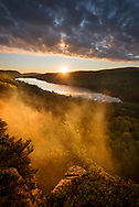 Fog rises from the valley below during a sunset over Lake of the Clouds<br />