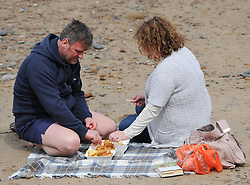 © Licensed to London News Pictures. 27/05/2013..Saltburn, England..A couple relax with some chips on the beach as they enjoy the warm bank holiday weather at Saltburn by the Sea in Cleveland....Photo credit : Ian Forsyth/LNP