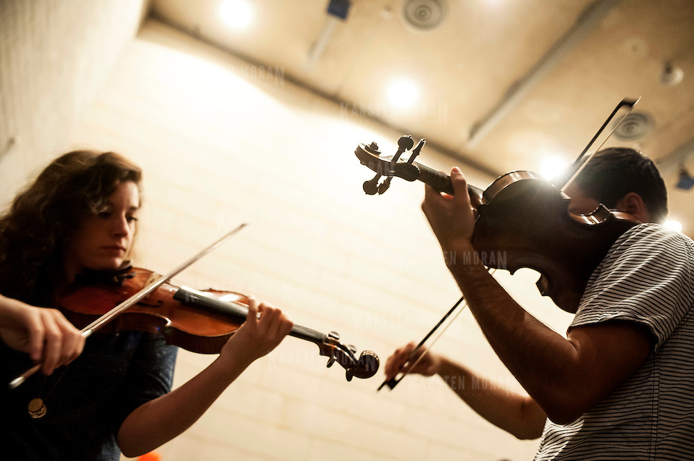 July 9, 2013 - Purchase, NY : Members of the National Youth Orchestra of the United States of America including, from left, Marianne Martinoli (from Monroe, Wash.), and Joseph Morag (from New York, N.Y.) get ready backstage as they prepare for rehearsal with conductor Valery Gergiev (not pictured) at SUNY Purchase's Performing Arts Center in Westchester on Tuesday afternoon. The Orchestra, a new project of Carnegie Hall's Weill Music Institute, is comprised of musicians aged 16-19, hand-picked from across the country. The program -- and orchestra -- will kick off its inaugural season with a performance at SUNY Purchase on Thursday evening, and then head off to perform in Washington DC,  Moscow, St. Petersburg, and London.  CREDIT: Karsten Moran for The New York Times