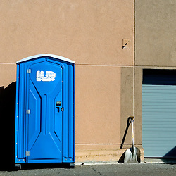 A shovel and a portable toilet at a construction site.