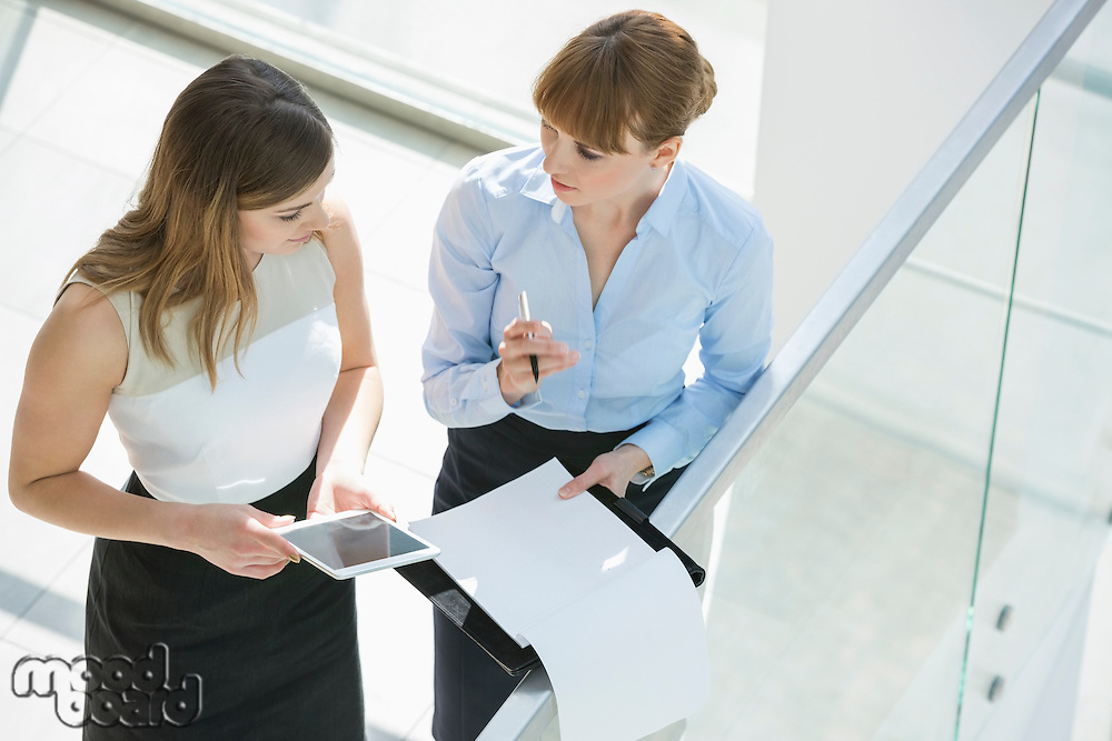 High angle view of businesswomen discussing over tablet PC and documents by railing in office