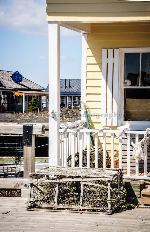 An old, broken lobster trap adorns a yellow store-front building in St-Andrews, NB Canada