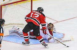 Mar 27, 2014; Newark, NJ, USA; Phoenix Coyotes goalie Thomas Greiss (1) stops New Jersey Devils right wing Damien Brunner (12) during the shootout at Prudential Center. The Coyotes defeated the Devils 3-2 in a shootout.