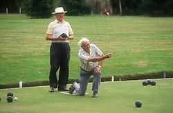Elderly men bowling on green,