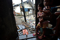 Young children sheltering from the rain, Tallo, Makassar, Sulawesi, Indonesia.