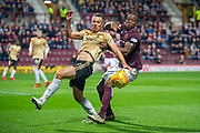 Andy Considine (#4) of Aberdeen FC holds off Uche Ikpeazu (#19) of Heart of Midlothian FC during the Betfred Scottish Football League Cup quarter final match between Heart of Midlothian FC and Aberdeen FC at Tynecastle Stadium, Edinburgh, Scotland on 25 September 2019.