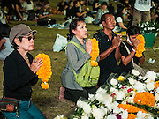 20 OCTOBER 2016 - BANGKOK, THAILAND:  People pray for the late Bhumibol Adulyadej, the King of Thailand, on Sanam Luang. Sanam Luang, the Royal Ceremonial Ground, is packed with people mourning the Monarch's death. The King died Oct. 13, 2016. He was 88. His death came after a period of failing health. Bhumibol Adulyadej was born in Cambridge, MA, on 5 December 1927. He was the ninth monarch of Thailand from the Chakri Dynasty and is also known as Rama IX. He became King on June 9, 1946 and served as King of Thailand for 70 years, 126 days. He was, at the time of his death, the world's longest-serving head of state and the longest-reigning monarch in Thai history.       PHOTO BY JACK KURTZ