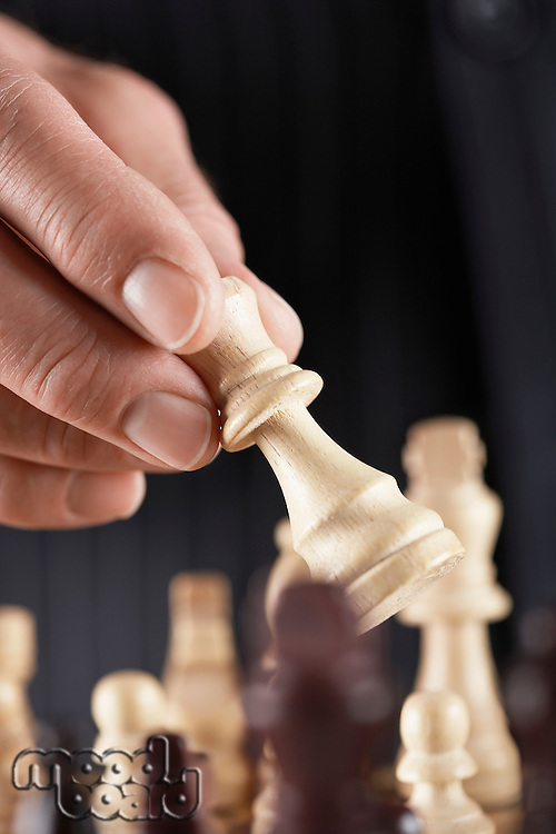 Man playing chess close-up of hand holding piece
