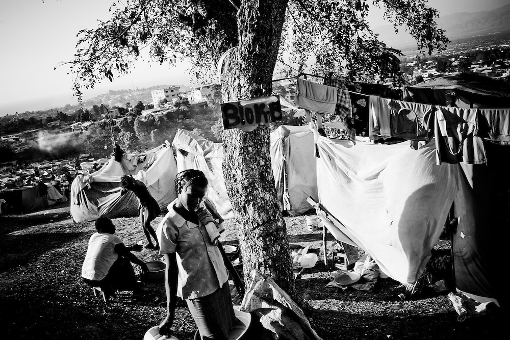 A woman carries water through a camp for those displaced by the recent earthquake in Petionville, outside Port-au-Prince, Haiti.