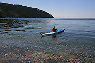 Woman in kayak paddles across placid, crystalline waters of Lake Superior at Terrace Bay, Ontario; Canada.