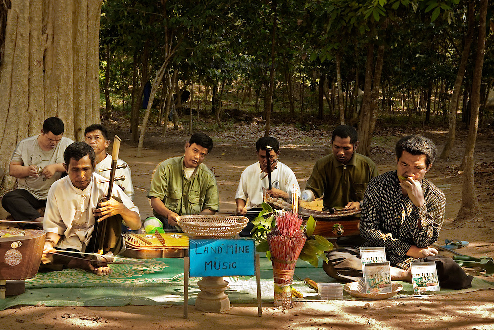 A group of seven survivors of land mine explosions earn a living by performing traditional Cambodian music in the Angkor Archaeological Park.  They also sell CDs of their performances.  They are seated on the ground in the dappled shade of the Angkor forest, their prosthetics and crutches scattered around them.  They are outside the temple of Banteay Srei, frequented by tourists.