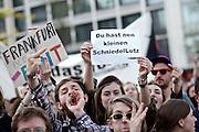 Frankfurt am Main | 21 Apr 2015<br /> <br /> Am Dienstag (21.04.2015) hielt die rassistische und islamfeindliche Gruppe PEGIDA (Patriotische Europ&auml;er gegen die Islamisierung des Abendlandes) an der Hauotwache neben der Katharinenkirche in Frankfurt am Main eine Mahnwache unter dem Motto &quot;Wir sind wieder da&quot; ab. Die Kundgebung war wie immer mit Hamburger Gittern abgesperrt und von starken Polizeikr&auml;ften bewacht. Etwa 1000 Menschen nahmen an den Gegenprotesten teil.<br /> Hier: Bei den Gegenprotesten h&auml;lt eine Demonstrantin ein kleines Plakat mit der Aufschrift &quot;Du hast nen kleinen SchniedelLutz&quot; hoch, sie bezieht sich mutmasslich auf den m&ouml;glicherweise sehr kleinen Penis des heute nicht anwesenden PEGIDA-Aktivisten Lutz Bachmann aus Dresden.<br /> <br /> &copy;peter-juelich.com<br /> <br /> [Foto Honorarpflichtig | No Model Release | No Property Release]