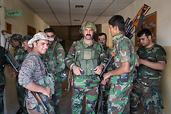 © Licensed to London News Pictures. 29/06/2014. Khanaqin, UK 29/06/2014. Khanaqin, Iraq. Kurdish peshmerga stand in the doorway to their barracks in Khanaqin, Iraq, after returning from fighting with ISIS insurgents in nearby Jalawla. Counted by Kurds as part of their homeland, fighting in the town of Jalawla now consists of occasional skirmishes and exchanges of fire between snipers and heavy machine guns on both sides.<br /> The peshmerga, roughly translated as those who fight, is at present engaged in fighting ISIS all along the borders of the relatively safe semi-automatous province of Iraqi-Kurdistan. Though a well organised and experienced fighting force they are currently facing ISIS insurgents armed with superior armament taken from the Iraqi Army after they retreated on several fronts.. Photo credit : Matt Cetti-Roberts/LNP
